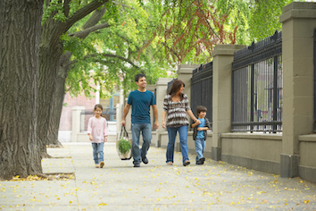 Family walking down sidewalk of neighborhood