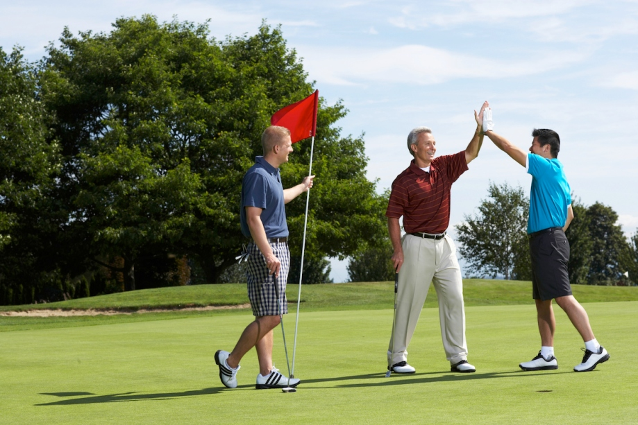 Golfers high fiving on putting green standing next to golfer holding flag